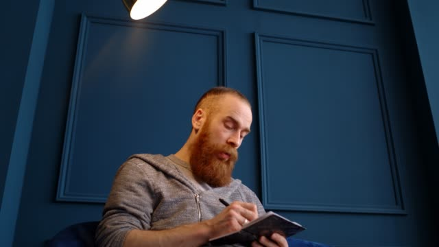 Portrait of a red-haired man with a beard sitting in the office