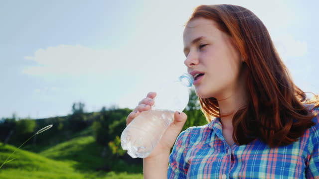 Portrait of a redheaded caucasian girl drinking water from a bottle. Picnic in a picturesque place video