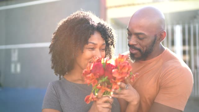 Portrait of a romantic couple - husband surprising wife with flowers