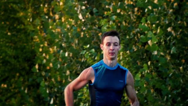 porträtt av en löpare man kör i park i skymningen, slow motion - tävlingsdistans bildbanksvideor och videomaterial från bakom kulisserna