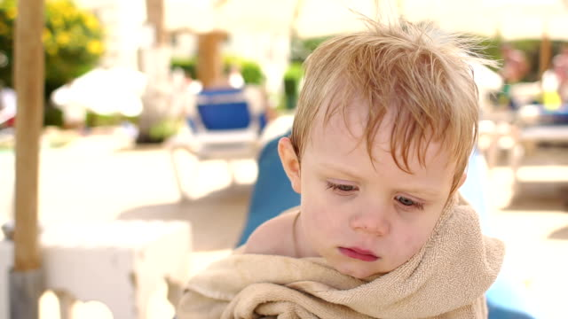 Portrait of a sad boy in beach towel by the pool. video