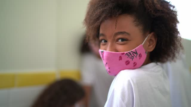 Portrait of a schoolgirl in the corridor using face mask at school