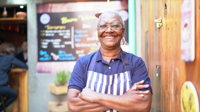 Portrait of a senior business owner standing in front of restaurant with arms crossed