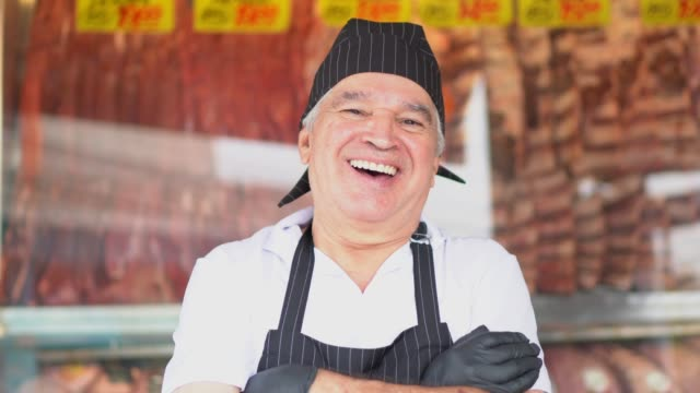 Portrait of a senior butcher standing with arms crossed in front of a butchers shop