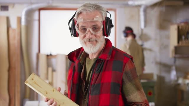 vidéos et rushes de ds portrait d'un charpentier aîné avec une barbe grise souriant dans son atelier - hlm