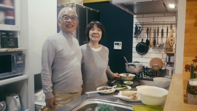 vídeos de stock e filmes b-roll de portrait of a senior couple with toshikoshi soba year-crossing noodles in the kitchen - tempura