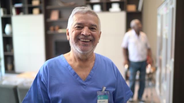 vidéos et rushes de verticale d'un docteur aîné, patient à l'arrière-plan - infirmier
