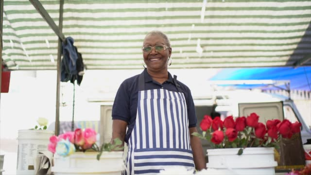 porträtt av en senior florist som arbetar på gatumarknaden - blomstermarknad bildbanksvideor och videomaterial från bakom kulisserna