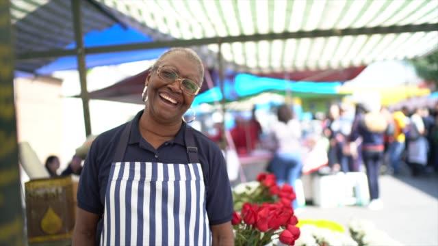 portrait of a senior florist working in a street market - video di bancarella video stock e b–roll