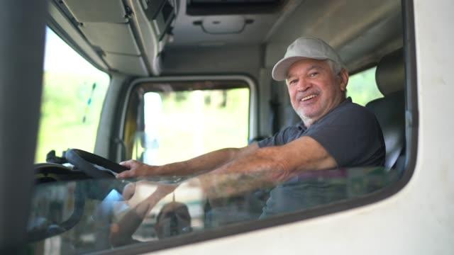 porträt eines älteren männlichen lkw-fahrers, der in der kabine sitzt - reliability stock-videos und b-roll-filmmaterial