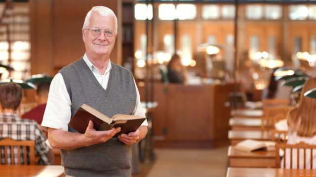 DS Portrait of a senior man holding a book standing in the library