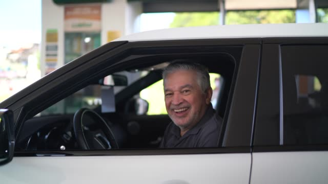 Portrait of a senior man inside his car at a gas station