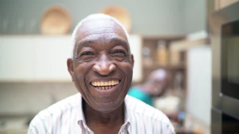 vidéos et rushes de verticale d'un homme aîné regardant l'appareil-photo - sourire