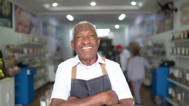 Portrait of a senior man standing with arms crossed in a natural product store