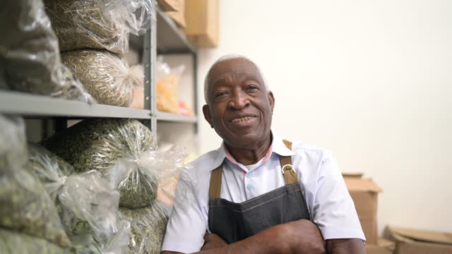 Portrait of a senior man standing with arms crossed in the storage room of a natural product store