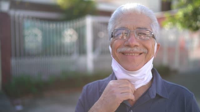 porträt eines älteren mannes, der gesichtsmaske auf der straße abnimmt - entfernt stock-videos und b-roll-filmmaterial