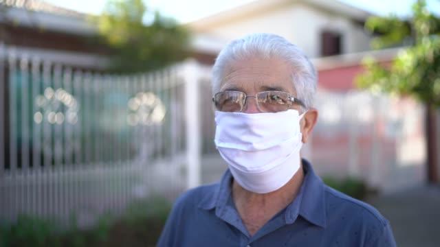 vídeos de stock e filmes b-roll de portrait of a senior man with face mask at street - isolated house, exterior