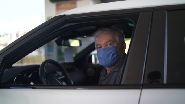 Portrait of a senior man with face mask inside his car at a gas station
