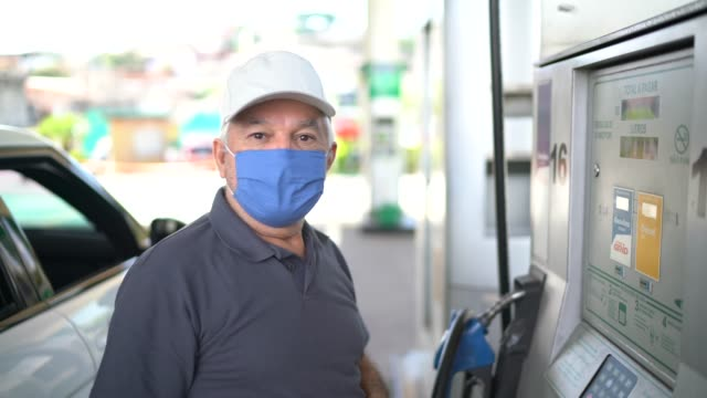 Portrait of a senior man with face mask refueling a car at a gas station