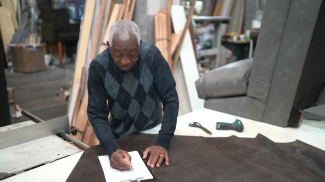 Portrait of a senior man working in an upholstery workshop, drawing Portrait of a senior man working in an upholstery workshop, drawing craftsperson stock videos & royalty-free footage