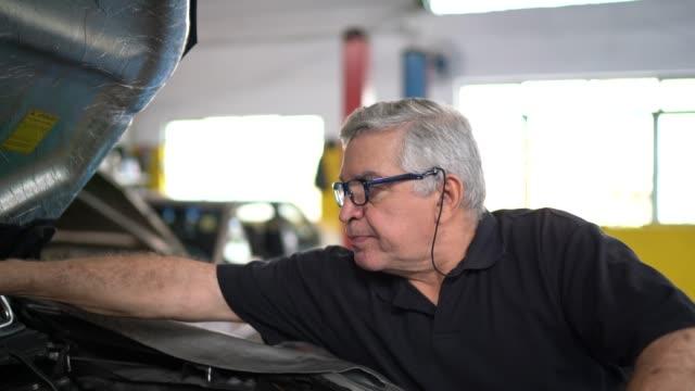 vídeos de stock, filmes e b-roll de retrato de um mecânico sênior em uma auto loja de reparo - brasileiro pardo