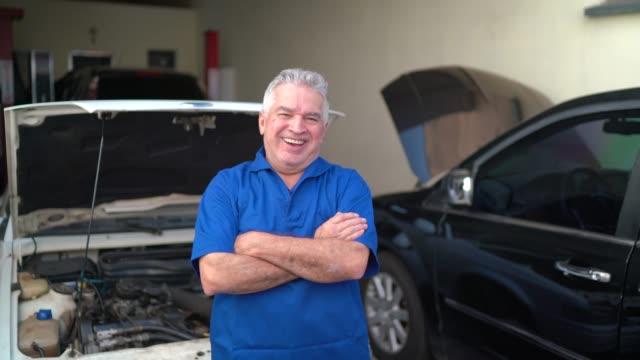 porträtt av en senior mekaniker stående med armarna korsade i en verkstad - mekaniker bildbanksvideor och videomaterial från bakom kulisserna