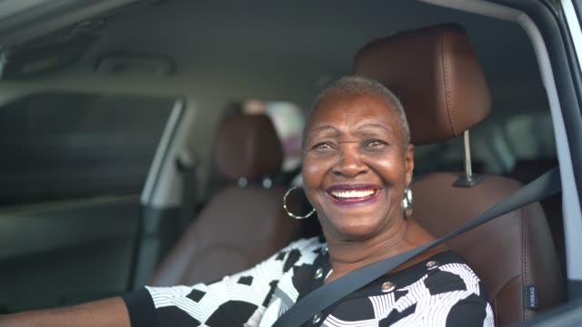 portrait of a senior woman driving a car - sorriso aperto video stock e b–roll