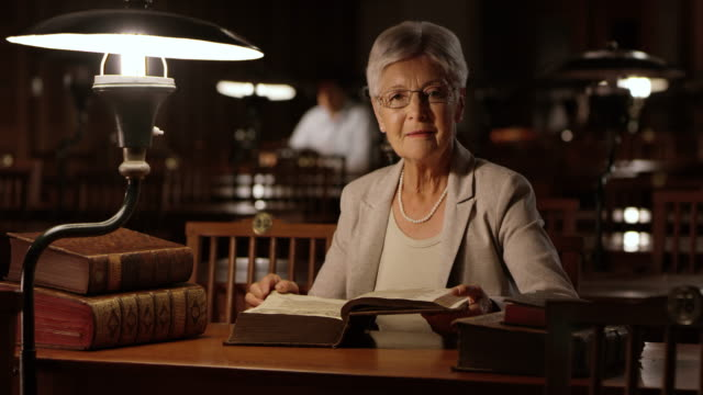 DS Portrait of a senior woman reading in the library at night video