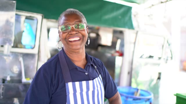 portrait of a senior woman working in a street market - canna da zucchero video stock e b–roll