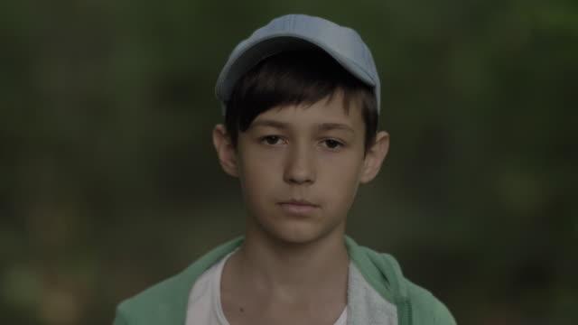 vídeos y material grabado en eventos de stock de retrato de un niño serio en una gorra de cerca mirando a la cámara, outdoos - sófbol