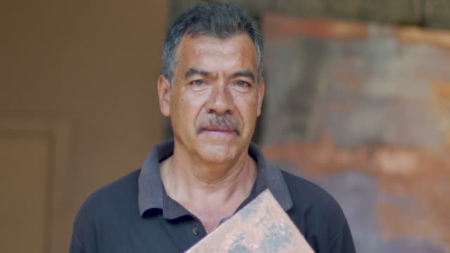 Portrait of a serious looking hispanic man holding a piece of copper