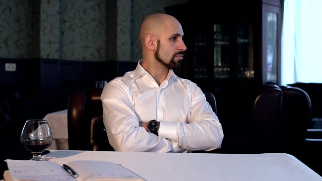 Portrait of a serious, strict man in restaurant. video