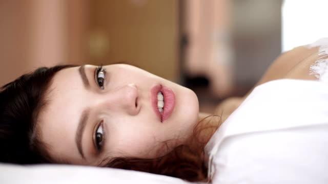 Retrato de un tranquilo en lencería sexy mujer tendido sobre el CAMA - vídeo