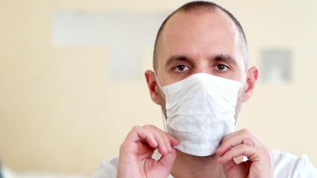 porträtt av en sjuk man som bär medicinsk mask. coronavirus koncept - face mask bildbanksvideor och videomaterial från bakom kulisserna