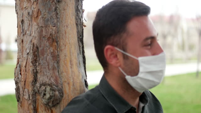 Portrait of a sick man wearing medical mask on a city public park bacground.