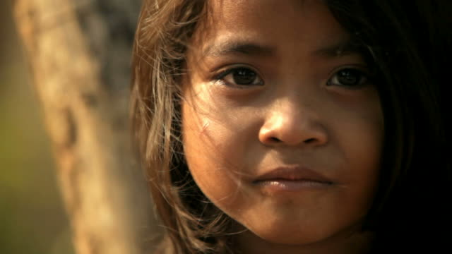 Portrait of a small Cambodian girl Portrait of a rural girl in Cambodia facing the camera. Tranquil scene with beautiful light and wind in her hair. Age 5. Taken in Cambodia, Asia, developing countries stock videos & royalty-free footage