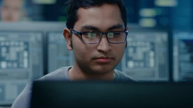portrait of a smart and handsome it specialist working on a personal computer. in the background bokeh shot of personal computers with screens in technologically advanced data research center - man evolution video stock e b–roll