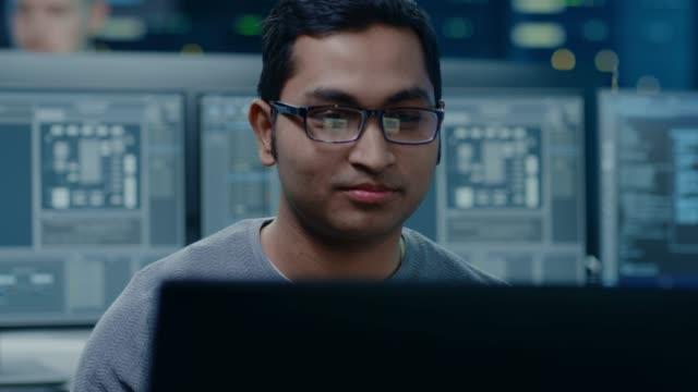 porträtt av en smart och snygg mjukvaru utvecklare bära glasögon arbeta på en persondator, smiles på kameran. i bakgrunden ofokuserade persondatorer med skärmar i tekniska rummet - server room bildbanksvideor och videomaterial från bakom kulisserna