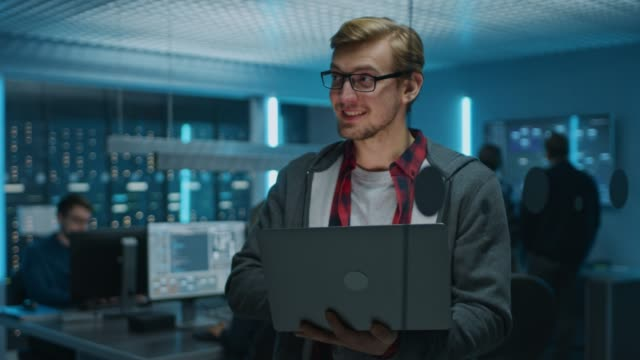 Portrait of a Smart Focused Young Man Wearing Glasses Holds Laptop. In the Background Technical Department Office with Specialists Working and Functional Data Server Racks Portrait of a Smart Focused Young Man Wearing Glasses Holds Laptop. In the Background Technical Department Office with Specialists Working and Functional Data Server Racks. Shot on RED EPIC-W 8K Helium Cinema Camera. it professional stock videos & royalty-free footage
