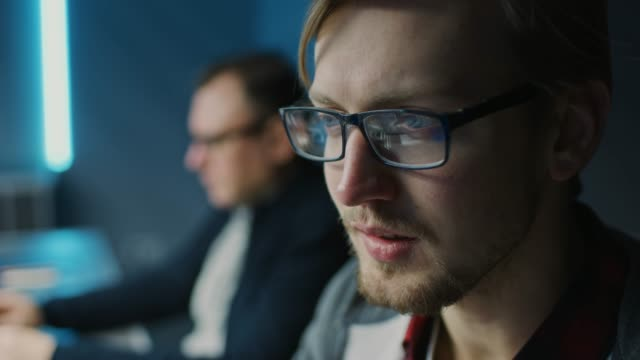 porträt eines smart focused young man wearing glasses, der an einem desktop-computer arbeitet. im hintergrund blurred office - ingenieur stock-videos und b-roll-filmmaterial