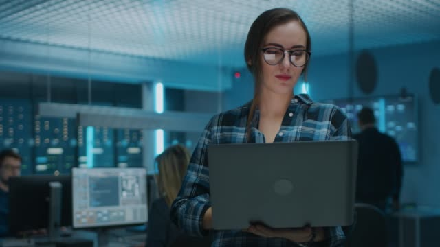 Portrait of a Smart Focused Young Woman Wearing Glasses Holds Laptop. In the Background Technical Department Office with Specialists Working and Functional Data Server Racks