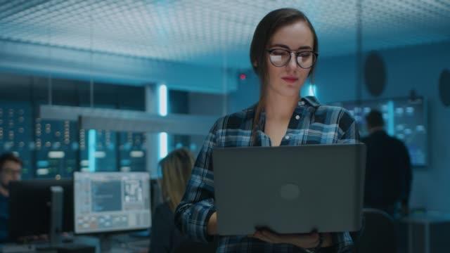 Porträt einer Smart Focused Young Woman Wearing Glasses Holds Laptop. Im Hintergrund Technische Abteilung mit Spezialisten arbeiten und funktionalen Daten-Server-Racks – Video