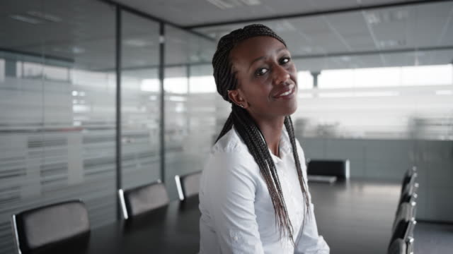 Portrait of a smiling African-American businesswoman in an empty conference room video