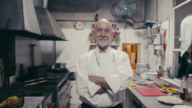 彼の台所で笑顔のアルゼンチンのシェフの肖像画 - 料理人点の映像素材/bロール