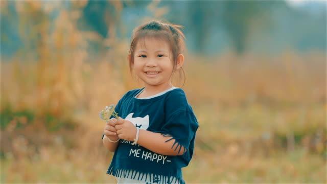 stockvideo's en b-roll-footage met portret van een glimlachend aziatische schattig meisje op zoek naar de camera en ruiken de bloemen op de weide - oost aziatische cultuur