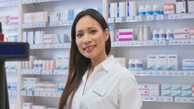 Portrait of a smiling Asian female pharmacist standing behind the counter