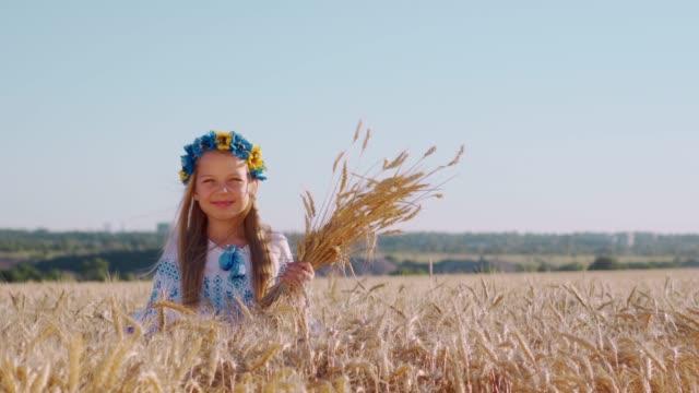vidéos et rushes de verticale d'une belle fille de sourire sur un champ de blé. une couronne sur la tête, les oreilles dans ses mains. une récolte riche. les gens qui vivent à la campagne. - seigle grain
