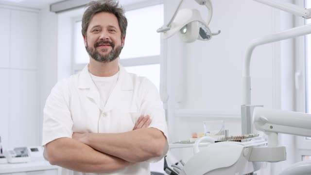 portrait of a smiling caucasian male dentist - dentist stock videos & royalty-free footage