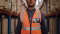 istock Portrait of a smiling confident warehouse worker in protecting hat standing with his arms crossed in a large warehouse looking at camera 1212669997