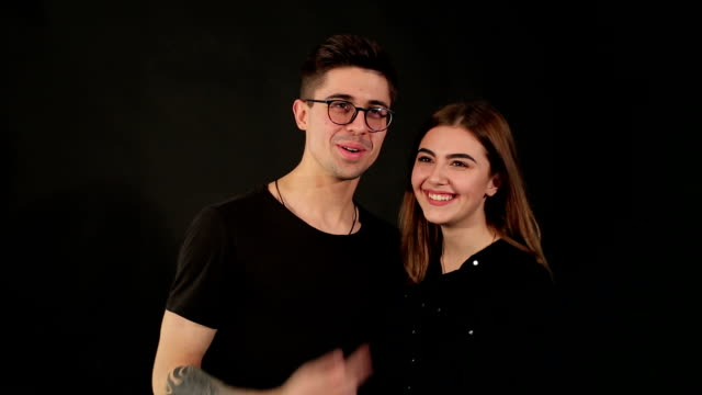 portrait of a smiling couple on a black background - brunette woman eyeglasses kiss man video stock e b–roll